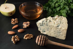 Tasty blue cheese with nuts and herbs on black stone board