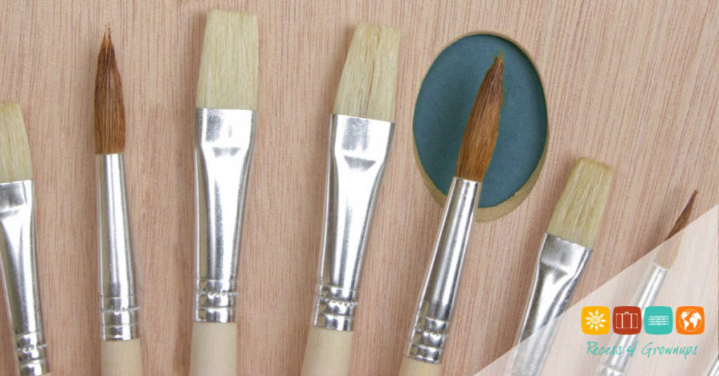 Wooden art palette with a brush on white background
