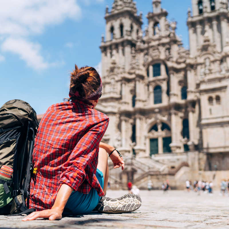 Woman backpacker piligrim siting on the Obradeiro square (plaza) in Santiago de Compostela