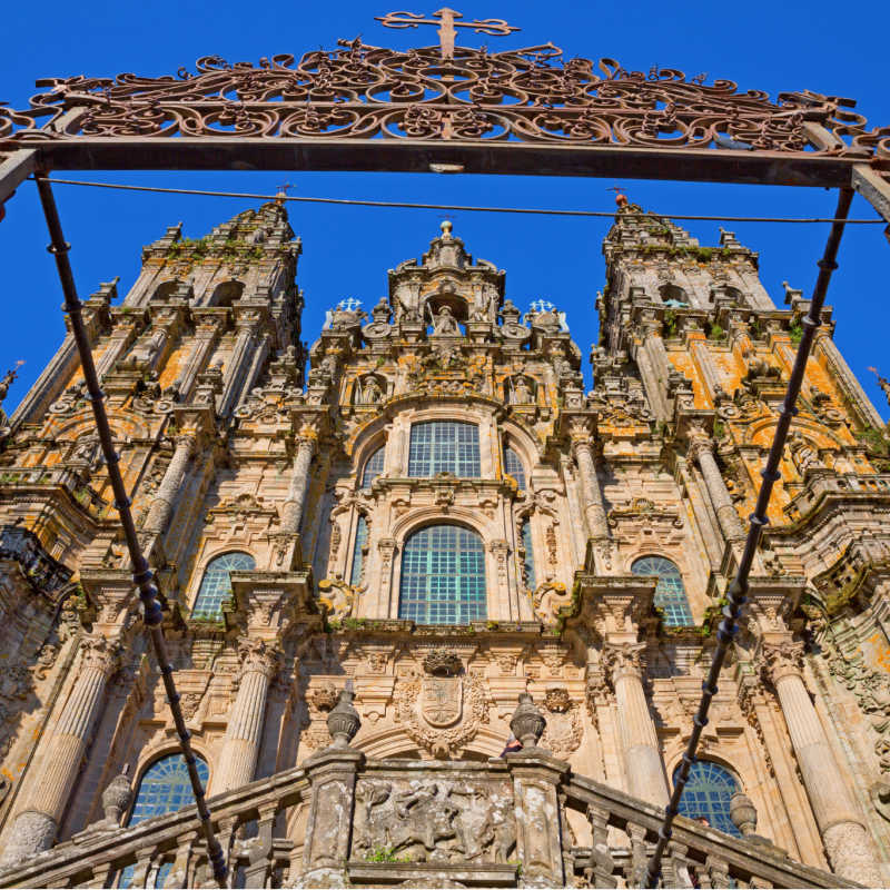 Facade of Cathedral of Santiago de Compostela with blue sky and grille
